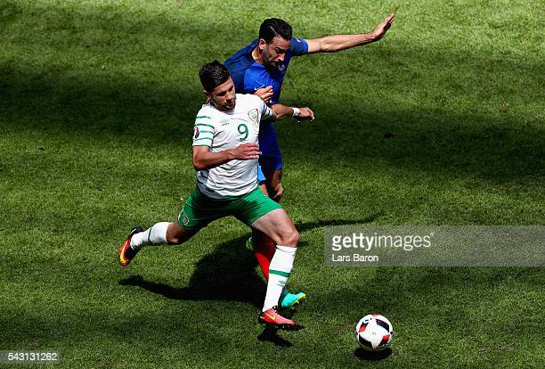 Adil Rami of France fouls Shane Long of Republic of Ireland resulting in an yellow card during the UEFA EURO 2016 round of 16 match between France...