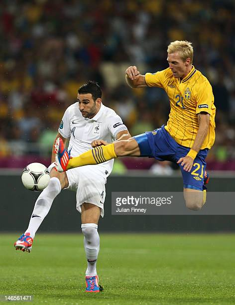 Adil Rami of France is challenged by Christian Wilhelmsson of Sweden during the UEFA EURO 2012 group D match between Sweden and France at The Olympic...