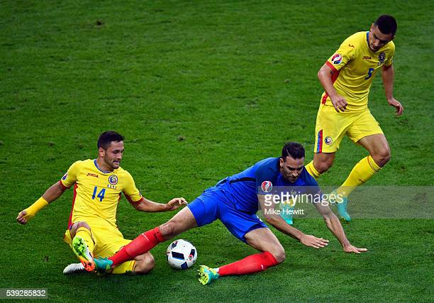 Adil Rami of France is tackled by Florin Andone of Romania during the UEFA Euro 2016 Group A match between France and Romania at Stade de France on...