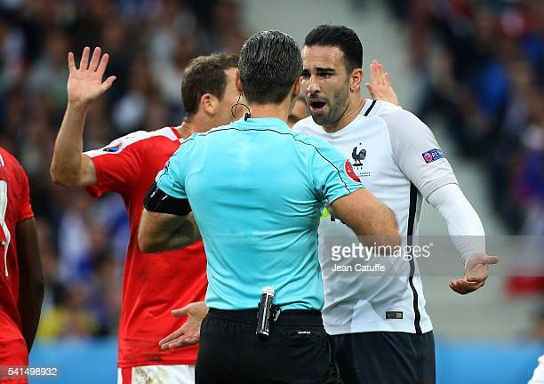 Adil Rami of France talks with Referee Damir Skomina of Slovenia during the UEFA EURO 2016 Group A match between Switzerland and France at Stade...