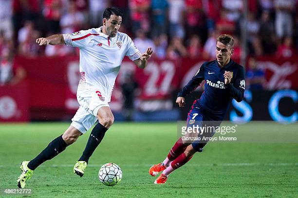 Adil Rami of Sevilla FC competes for the ball with Antoine Griezmann of Atletico de Madrid during the La Liga match between Sevilla FC and Club...