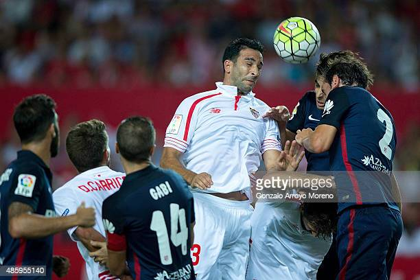Adil Rami wins the header after Tiago Mendes of Atletico de Madrid <nd his teammate Diego Godin during the La Liga match between Sevilla FC and Club...