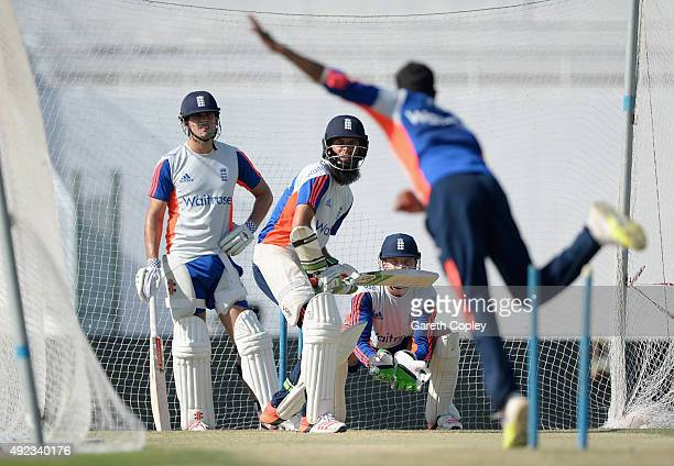 Adil Rashid of England bowls to Moeen Ali watched by captain Alastair Cook during a nets session at Zayed Cricket Stadium on October 12 2015 in Abu...