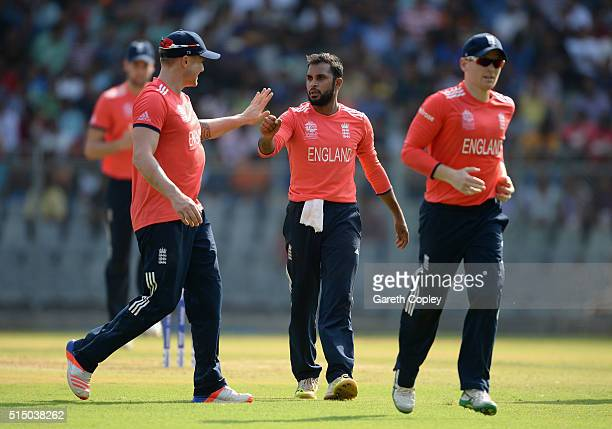 Adil Rashid of England celebrates with Jason Roy and captain Eoin Morgan after dismissing Mitchell Santner of New Zealand during the ICC Twenty20...