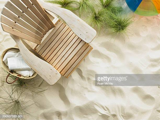 Adirondack chair and beach ball on sand, overhead view