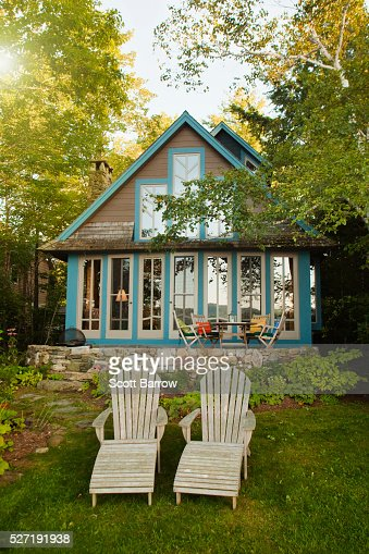 Adirondack chairs beside a summer cottage : Stock Photo