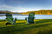Photo of two Green of Adirondack Chairs on a Lawn in front of a Lake at Sunset. The other side of the Lake is Covered with Autumnal Trees.