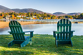 Green Adirondack Chairs on the Shore of Mirror Lake in Lake Placid, Adirondack Mountains, NY, on a Clear Autumn Day