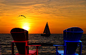 Red and blue Adirondack chairs with sailboat on Lake Michigan at sunset.