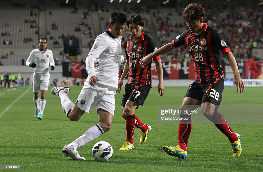Adisak Kraisorn of Buriram United in action with Kim Nam-Chun and Kim Chi-Woo of FC Seoul during the AFC Champions League Group E match between FC Seoul and Buriram United at Seoul World Cup Stadium on May 1, 2013 in Seoul, South Korea.