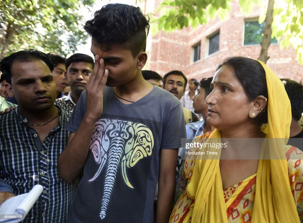 Aditya, son of Rishi Pal with other family members, after Rishi Pal was dead and left three people unconscious during sewer cleaning at Lok Nayak Jai Prakash Narayan Hospital, on August 20, 2017 in New Delhi, India. Rishi Pal, 40, along with Bishan, 30, Kiran Pal, 25, and Sumit, 30, fell unconscious after inhaling poisonous gases while cleaning the sewer.