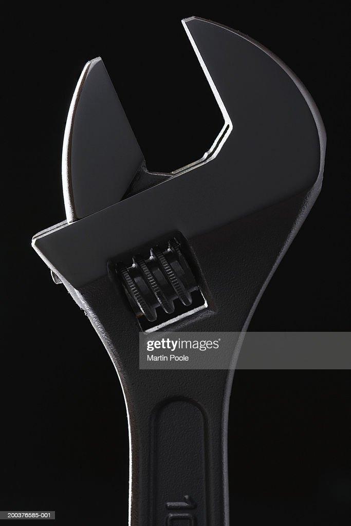 Adjustable spanner against black background, close-up (backlit)