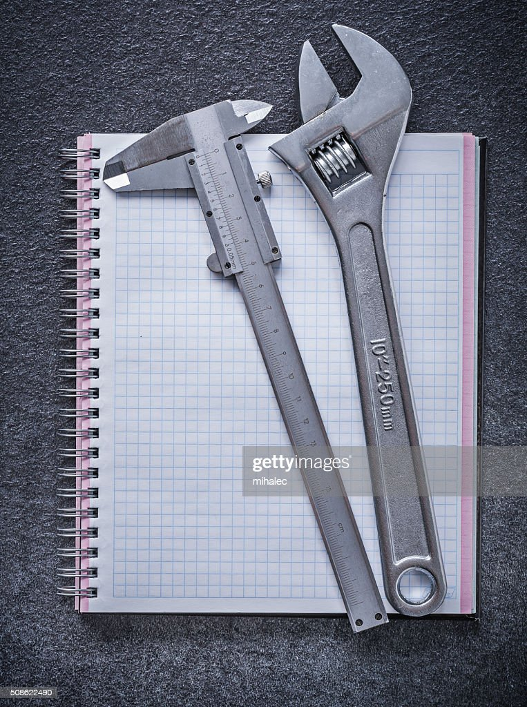 Adjustable wrench slide caliper notebook on black background con : Stock Photo