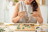 Woman using pliers to adjust malachite gemstones