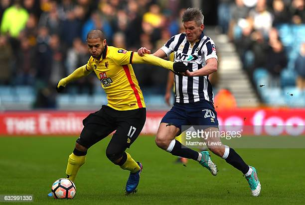 Adlene Guedioura of Watford holds back Steve Morison of Millwall during The Emirates FA Cup Fourth Round match between Millwall and Watford at The...