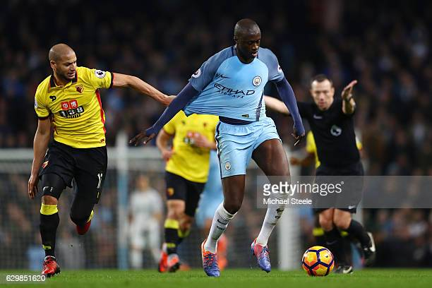 Adlene Guedioura of Watford pulls on Yaya Toure of Manchester City shirt during the Premier League match between Manchester City and Watford at...
