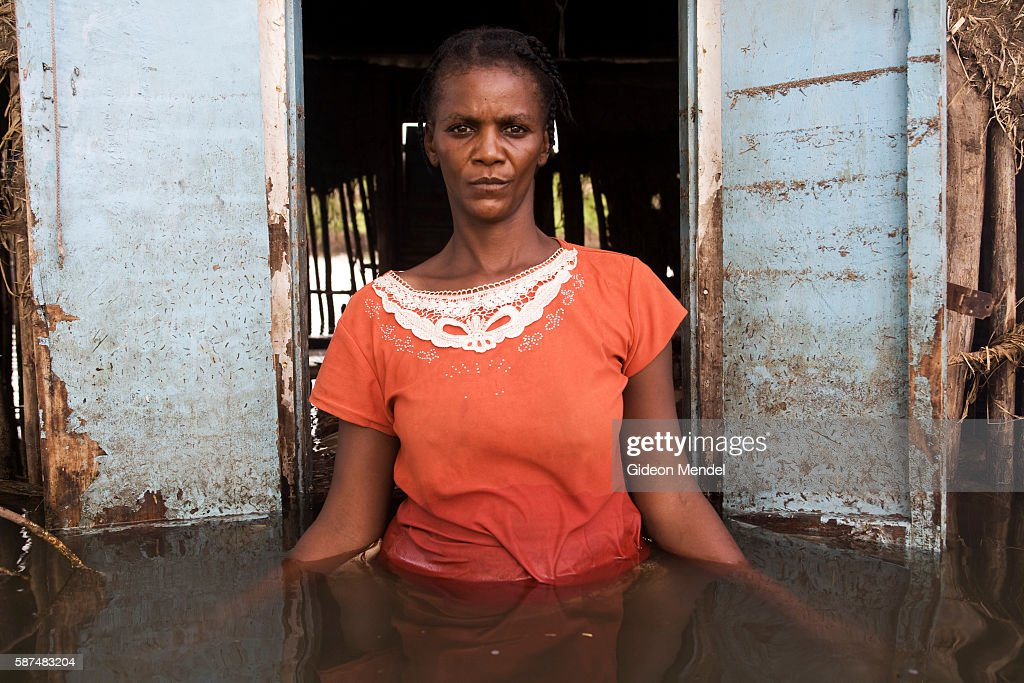 Adlene Pierre aged 35 faces the camera in front of one of the windows of her flooded house in Savanne Desole on the outskirts of the city of Gonaives...