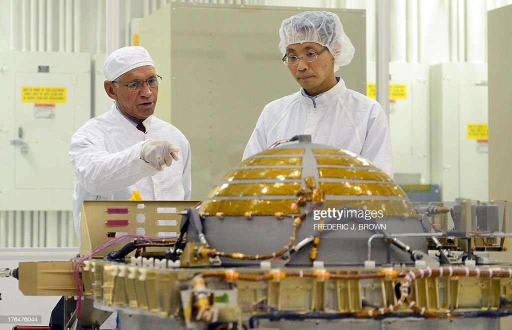 Administrator Charles Bolden (L) comments on the propulsion subsystem unit while walking with Lead System Engineer for the SMAP Satellite, Wayne Lee (R), at the Jet Propulsion Laboratory in Pasadena, California on August 13, 2013, where NASA Administrator Charles Bolden came to see the progress and assembly of the Soil Moisture Active Passive (SMAP) satellite presently under construction and due to launch in October 2014. SMAP will produce global maps of soil moisture for tracking water availability around the planet, and will also detect winter freeze and spring thaw to track changes in growing season patterns, allowing scientists to determine how much carbon plants take up from the atmosphere each year. AFP PHOTO/Frederic J. BROWN
