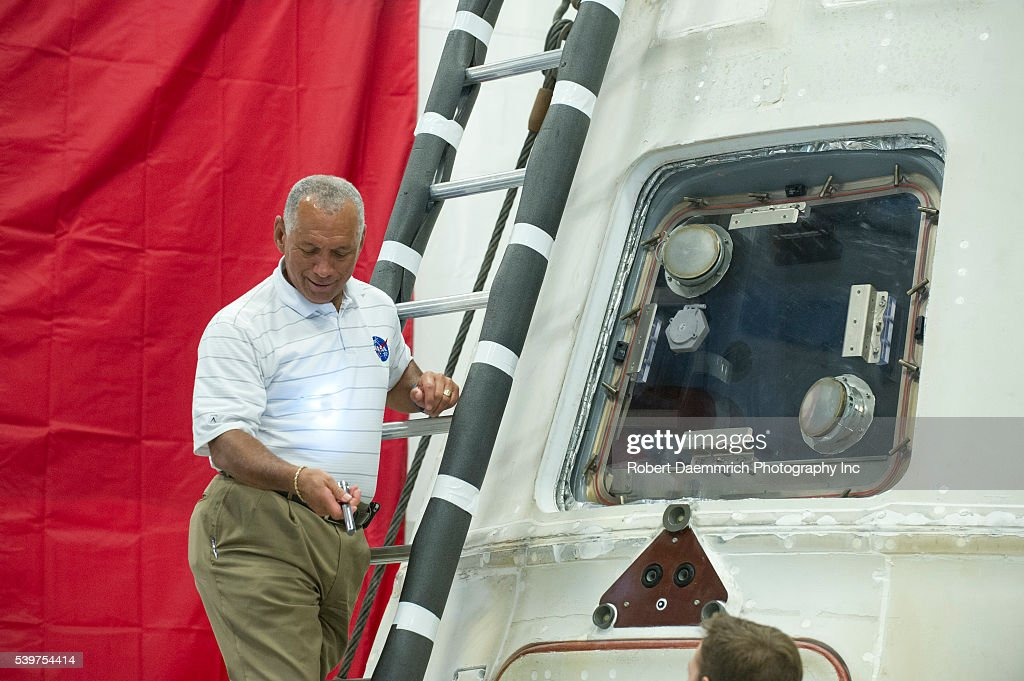 NASA administrator Charles Bolden grabs a flashlight to look inside the private Dragon spacecraft that returned to earth May 31st after delivering...