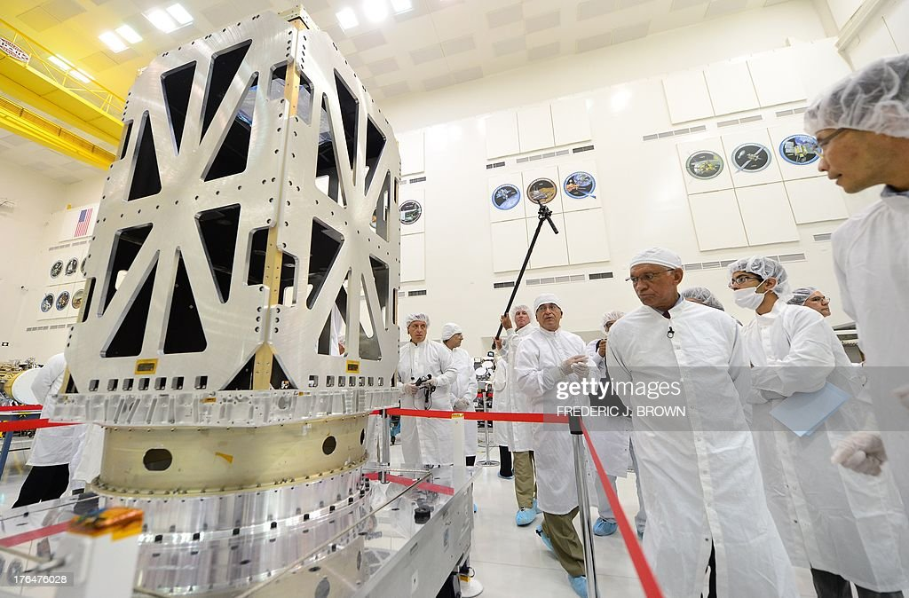 Administrator Charles Bolden tours the Spacecraft Assembly Facility Cleanroom at the Jet Propulsion Laboratory in Pasadena, California on August 13, 2013, to see the progress and assembly of the Soil Moisture Active Passive (SMAP) satellite (L) presently under construction and due to launch in October 2014. SMAP will produce global maps of soil moisture for tracking water availability around the planet, and will also detect winter freeze and spring thaw to track changes in growing season patterns, allowing scientists to determine how much carbon plants take up from the atmosphere each year. AFP PHOTO/Frederic J. BROWN