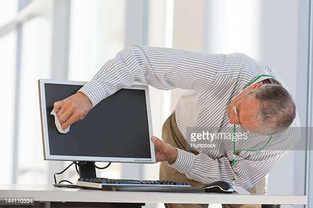 Administrator cleaning a computer screen