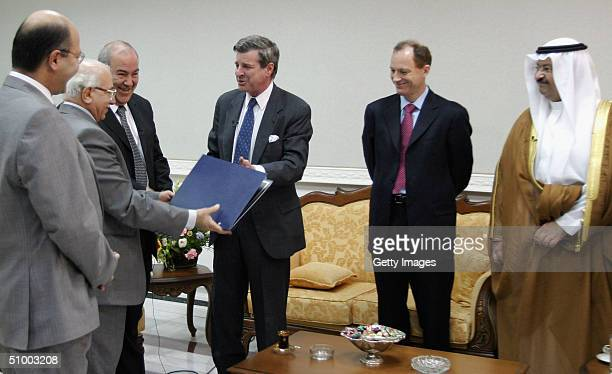 S administrator Paul Bremer flanked by Iraqi interim Prime Minister Iyad Allawi and Bremer's deputy David Richmond as Iraqi President Ghazi alYawar...