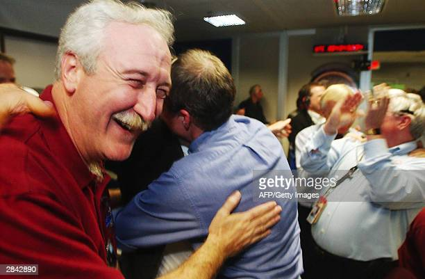 Administrator Sean O'Keefe left hugs Principal Investigator Steve Squyres in the control room at NASA's Jet Propulsion Laboratory as they get a...