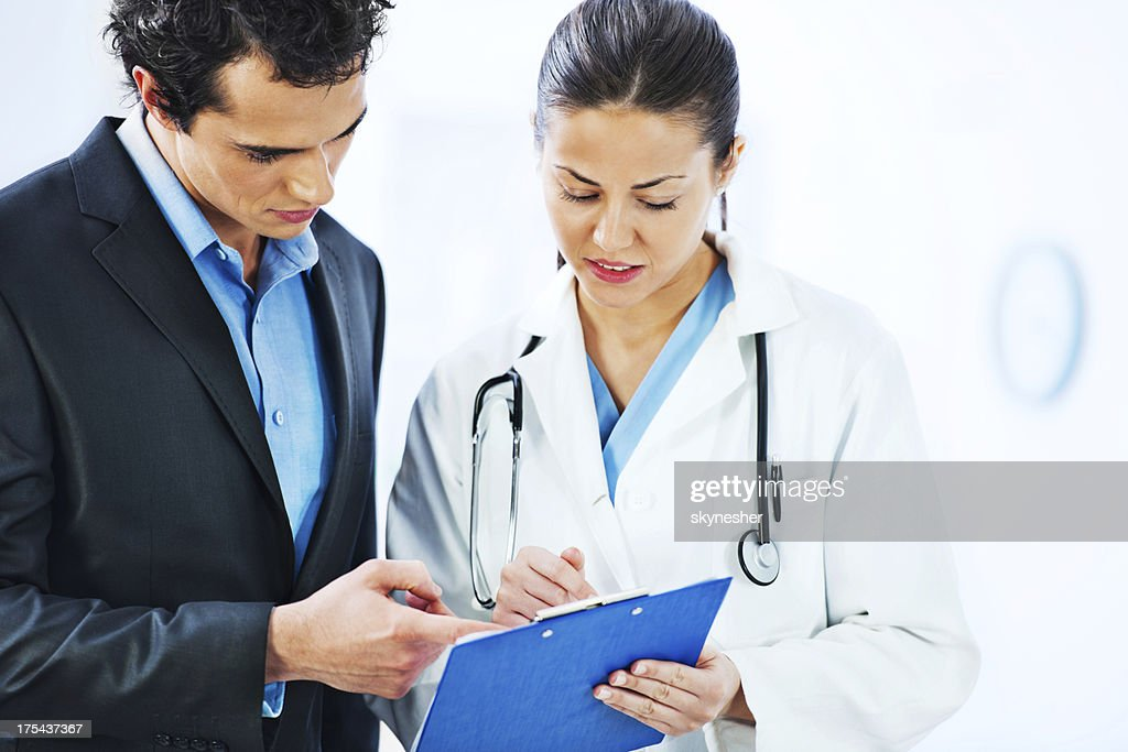 Administrator talking to a female doctor : Stock Photo