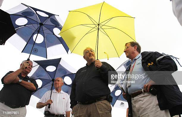 Administrator W Craig Fugate center huddles under umbrellas with local mayors and other officials at the Biloxi Lighthouse in Biloxi Mississippi...