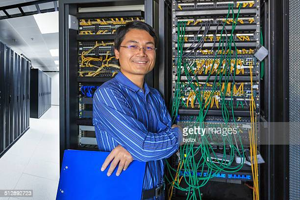 Administrator working on a server room with smile