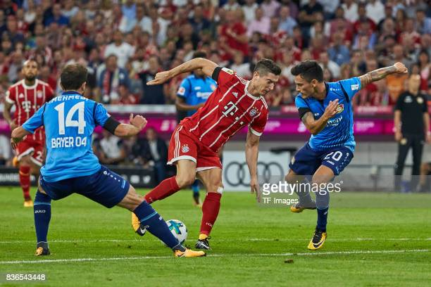 Admir Mehmedi and Charles Aranguiz and Robert Lewandowski of Muenchen battle for the ball during the Bundesliga match between FC Bayern Muenchen and...