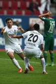 Admir Mehmedi of Freiburg celebrates the first goal with Francis Coquelin of Freiburg and Daniel Baier of Augsburg looks dejected during the...