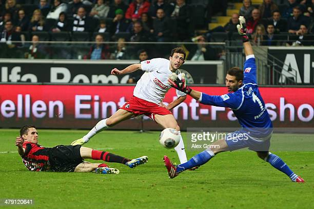 Admir Mehmedi of Freiburg tries to score against Johannes Flum and goalkeeper Kevin Trapp of Frankfurt during the Bundesliga match between Eintracht...