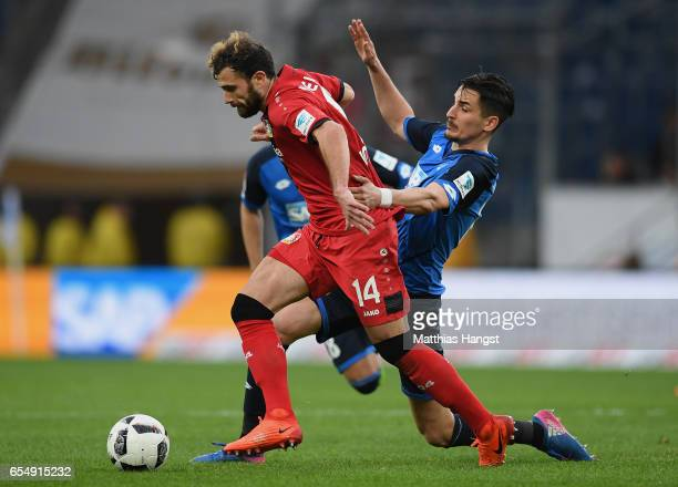 Admir Mehmedi of Leverksuen is challenged by Benjamin Huebner of Hoffenheim during the Bundesliga match between TSG 1899 Hoffenheim and Bayer 04...