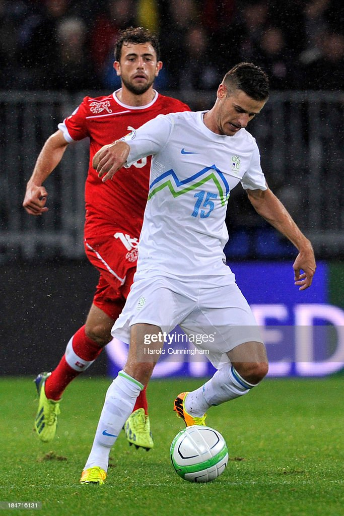 Admir Mehmedi of Switzerland and Andraz Struna of Slovenia in action during the FIFA 2014 World Cup Qualifier match between Switzerland and Slovenia match held at Stade de Suisse on October 15, 2013 in Bern, Switzerland.