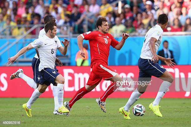 Admir Mehmedi of Switzerland controls the ball against Yohan Cabaye and Raphael Varane of France during the 2014 FIFA World Cup Brazil Group E match...