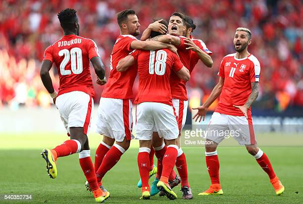 Admir Mehmedi of Switzerland is crowded out by team mates after he scored his teams first goal during the UEFA EURO 2016 Group A match between...