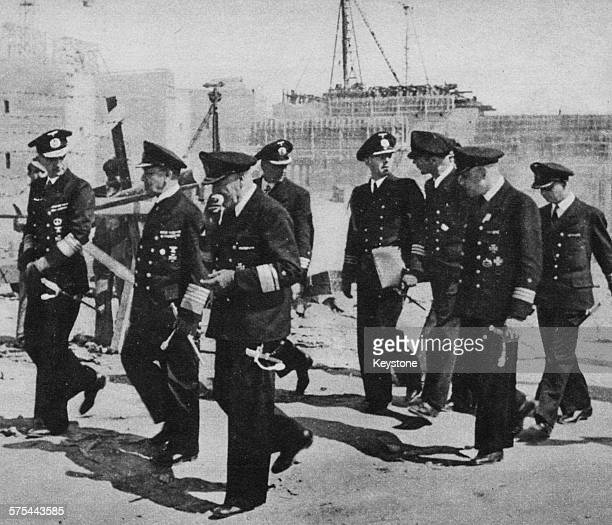 Admiral Erich Raeder and Admiral Karl Donitz with a group of naval officers inspecting a Uboat base during World War Two circa 1943