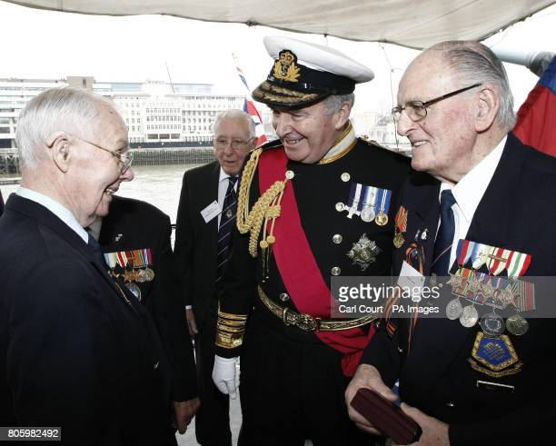 Admiral the Lord West speaks to World War II Russian Convoy veterans after a ceremony on board HMS Belfast in which 14 veterans were presented with...