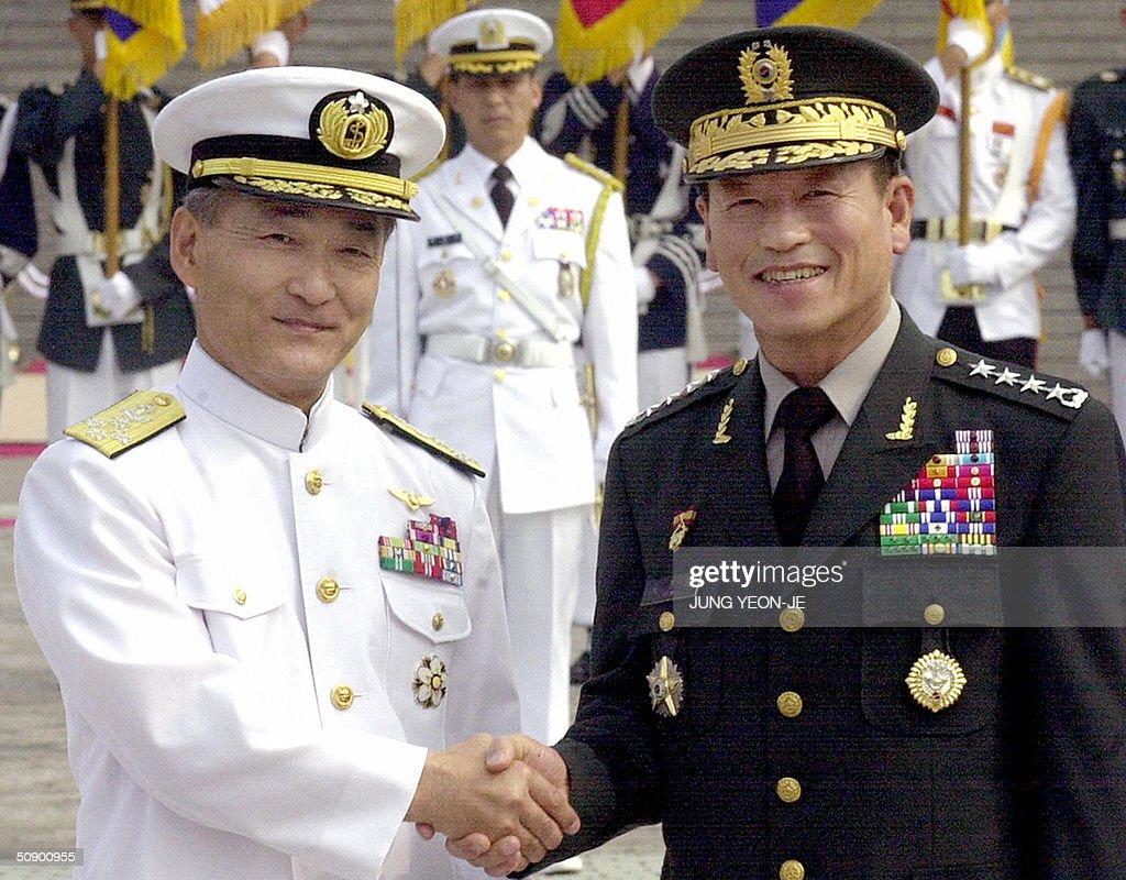 Admiral Toru Ishikawa chairman of the Japanese SelfDefense Force's Joint Staff Council shakes hands with his South Korean counterpart Kim Jonghwan...