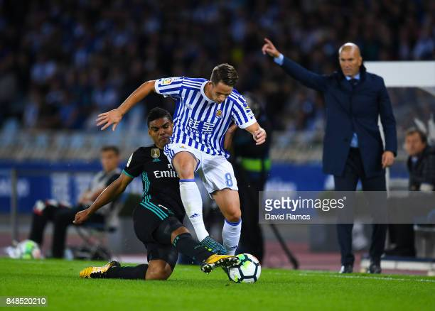Adnan Januzaj of Real Sociedad de Futbol competes for the ball with Carlos Enrique Casimiro of Real Madrid CF during the La Liga match between Real...