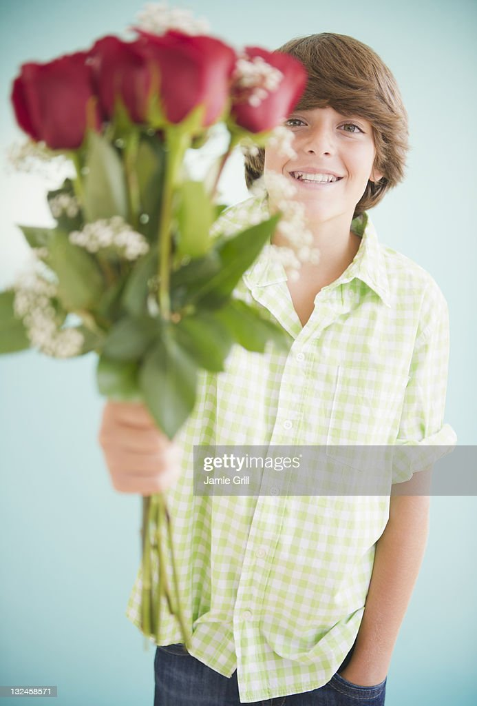 Adolescent boy holding out bouquet of roses : Stock Photo