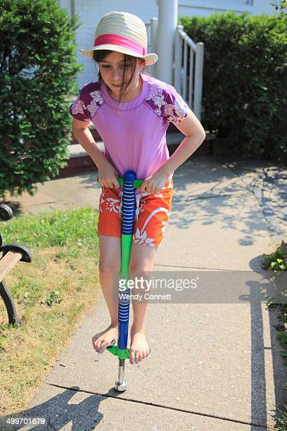 Adolescent girl playing on pogo stick