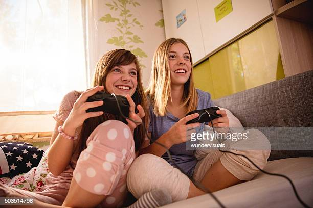 Adolescent girls playing computer games at pyjama party