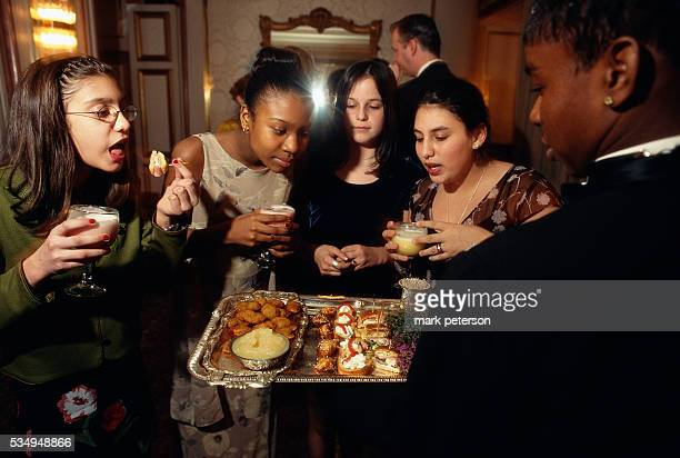 Adolescent girls select appetizers from a tray during a bat mitzvah celebration for 13yearold Ali Green The reception takes place at a ballroom on...