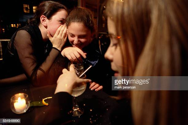 Adolescent girls whisper to each other during a bat mitzvah celebration for 13yearold Ali Green The reception takes place at a ballroom on...