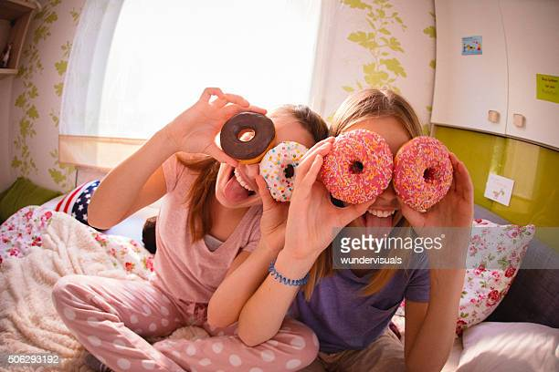 Teenager-Mädchen mit bunten Donuts auf Ihre Augen