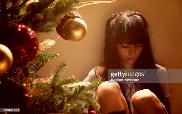 Adolescente leyendo al lado del árbol de Navidad.