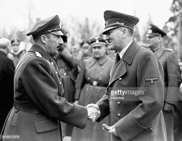 Adolf Hitler and Boris King of Bulgaria shake hands as several German officials look on