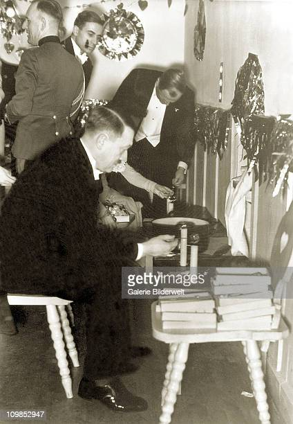 Adolf Hitler celebrating new Year's Eve at his residence the Berghof near Berchtesgaden Germany 31st December 1938 He is busy casting lead as are...